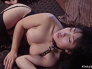 Redhead lesbian mistress in black lingerie spanks Asian slave then makes her eat pussy before anal fucks her with strap on cock